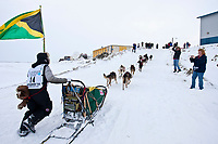 The first ever Jamaican musher Newton Marshall runs up from the Bering Sea onto Front Street in Nome as he holds the Jamaican flag during the 2010 Iditarod