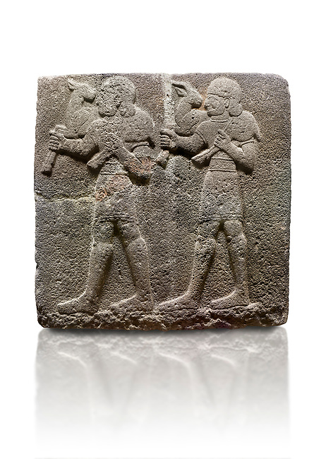 Hittite monumental relief sculpted orthostat stone panel of a Procession Basalt, Karkamıs, (Kargamıs), Carchemish (Karkemish), 900-700 B.C.  Anatolian Civilisations Museum, Ankara, Turkey. Young male servants of Kubaba while carrying sacrificial animals on their shoulders. <br /> <br /> Against a white background.