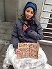 Young woman begging with message on cardboard.<br />