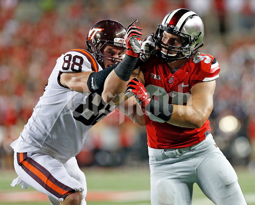 Ohio State Buckeyes defensive lineman Joey Bosa (97) takes on Virginia Tech Hokies tight end Ryan Malleck (88) during Saturday's NCAA Division I football game between the Ohio State Buckeyes and the Virginia Tech Hokies at Ohio Stadium in Columbus on September 6, 2014. Virginia Tech led at halftime, 21-7. (Dispatch Photo by Barbara J. Perenic)