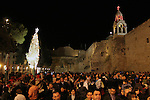 Palestinians gather around the lit Christmas tree outside the Church of the Nativity in the West Bank city of Bethlehem on December 15, 2009. Christians Pilgrims and tourists are expected to visit Bethlehem, the alleged birthplace of Jesus Christ, this coming Christmas. According to the Christmas story, the three Kings who visited Jesus Christ in Bethlehem followed a star until they found him in a manger in this now holy town.Photo by Najeh Hashlamoun