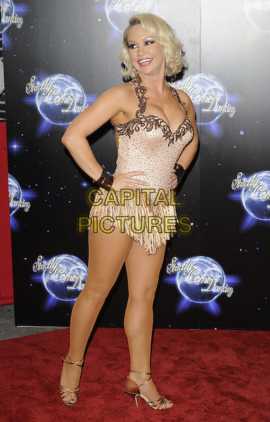 KRISTINA RIHANOFF .At the Strictly Come Dancing Launch Show TV recording, London, England, UK, September 8th 2010..full length  halterneck top costume dress  beige sparkly strappy gold sandals hands on hips cuffs tassels .CAP/CAN.©Can Nguyen/Capital Pictures.