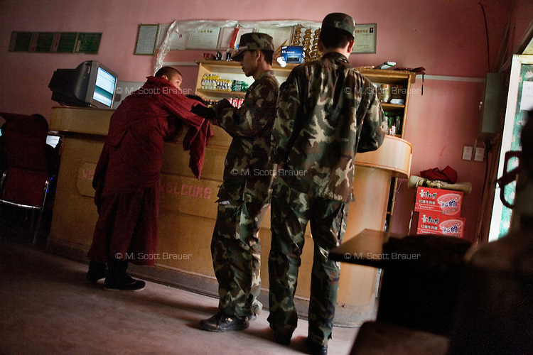 Young Tibetan Buddhist monks and Chinese military soldiers wait for an attendant in an internet cafe in Xiahe, Gansu, China.  Xiahe, home of the Labrang Monastery, is an important site for Tibetan Buddhists.  The population of the town is divided between ethnic Tibetans, Muslims, and Han Chinese.