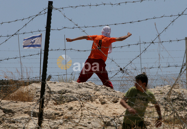 a Palestinian protestor throws stones towards Israeli soldiers during a demonstration against the Israeli controversial separation barrier in the West Bank village of Bilin near Ramallah,May 29, 2009.APAIMAGES PHOTO /Issam rimawi