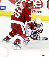 Wisconsin's John Ramage takes down UNO's Brock Montpetit. Ramage was whistled for tripping on the play. No. 16 UNO beat No. 7 Wisconsin 4-1 in front of a school-record crowd of 15,137 Friday night at Qwest Center Omaha.  (Photo by Michelle Bishop)