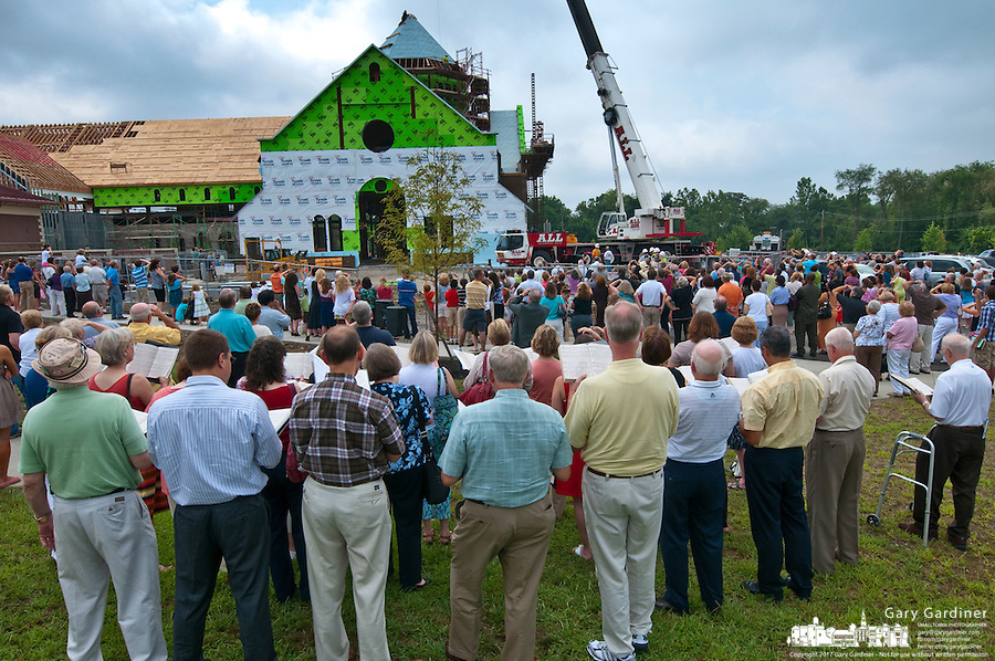 Parishioners watch as a gold cross is raised to the top of the St. Paul Catholic Church's new building on North State Street.