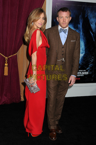 Jacqui Ainsley & Guy Ritchie.The World Premiere of 'Sherlock Holmes: A Game of Shadows' held at The Village Theatre in Brentwood, California, USA..December 6th, 2011.full length red dress brown suit waistcoat couple silver clutch bag bow tie maxi side.CAP/ADM/BP.©Byron Purvis/AdMedia/Capital Pictures.