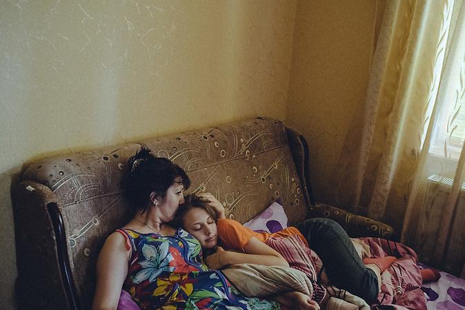 Katrine with mother inside her room taking rest. Ribnita, Transnistria