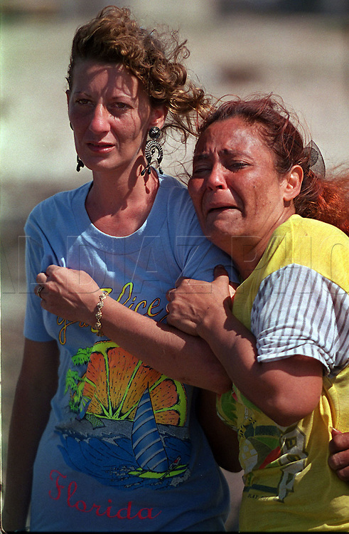 8/1994-Al Diaz/Miami Herald--In 1994 Cuban balseros turned the tiny fishing village of Cojimar into a major point of embarkation for thousands seeking a better life. Here, Idelisa Gonzalez, right,  cries and prays to God as her only daughter leaves Cojimar, Cuba on a makeshift raft. The woman at left is unidentified.
