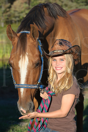Girl with horse in close up portrait, pretty blonde in cowboy hat, summer evening in Pennsylvania, PA, USA.