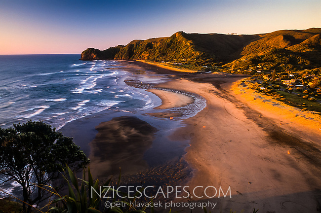 Sunset over Piha Beach and its small township west of Auckland, West Auckland, New Zealand