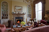 A cheerful living room with an open fire burning within an ornately carved fire surround