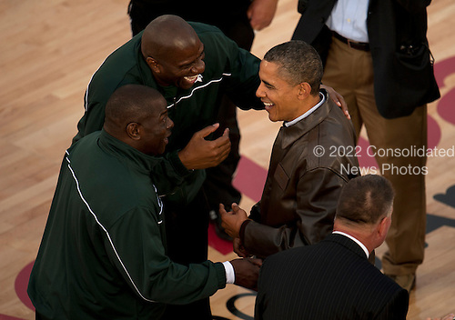 """United States President Barack Obama, left, is greeted on the court by NBA Hall of Fame basketball player Earvin """"Magic"""" Johnson, center, and Michigan State University assistant coach Mike Garland at the Quicken Loans Carrier Classic on Friday, November 11, 2011 aboard the Nimitz-class aircraft carrier USS Carl Vinson (CVN 70) in San Diego, California. Carl Vinson hosted Michigan State University and the University of North Carolina for an NCAA basketball game. .Mandatory Credit: James R. Evans - U.S. Navy via CNP"""