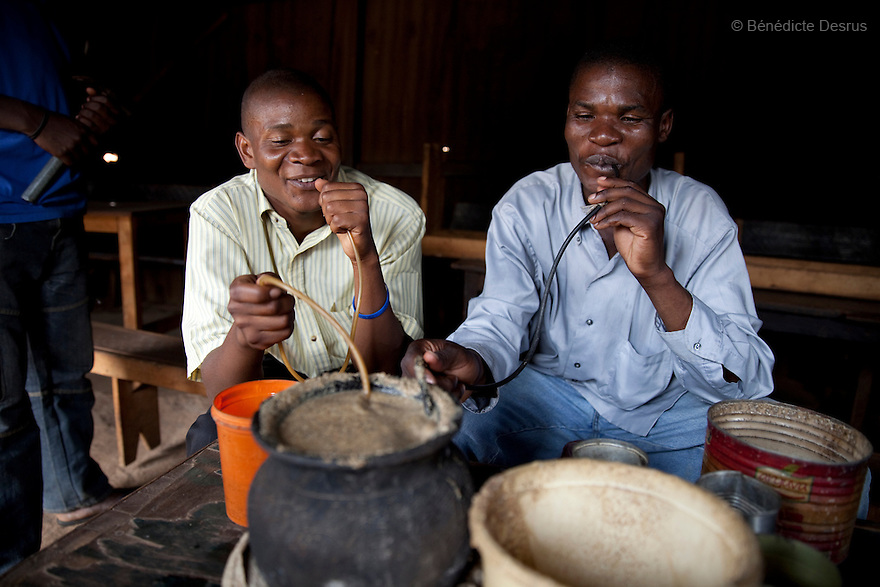 Two Kenyans men drink busaa, a traditional fermented beer, from a common pot using long straws - in a busaa club at midday in a Nairobi slum on March 27, 2013. Busaa is made by crudely fermenting maize, millet, sorghum or molasses. At Kshs 35 per liter it is much cheaper than a Kshs120 half-liter bottle of commercial beer. The local brew was legalised in 2010 and since then busaa clubs have become increasingly popular. Drinking is on the rise in Kenya, especially among young people. Photo: Benedicte Desrus