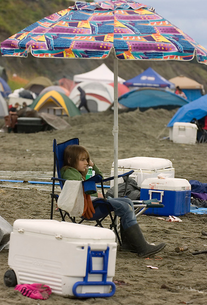 Rose Baklanov watches her family dipnet sockeye salmon from the Kenai River at its mouth in Kenai, Alaska, while sitting at the edge of a temporary tent city that returns to the beach every year, just like the salmon.