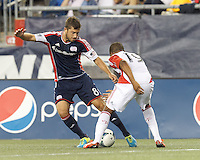 New England Revolution defender Chris Tierney (8) dribbles as Toronto FC midfielder Reggie Lambe (19) defends. In a Major League Soccer (MLS) match, Toronto FC (white/red) defeated the New England Revolution (blue), 1-0, at Gillette Stadium on August 4, 2013.