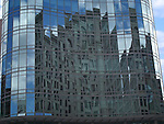 A mosaic-like reflection of a historic church and a blue, blue sky in the all glass building across the street.