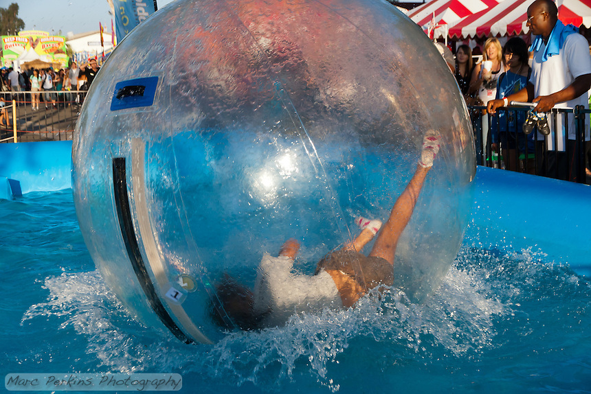 A girl falls inside an inflated water walking ball in an inflatable pool at the 2011 Orange County Fair.  I have a six-picture sequence of her falling as a separate image.   The girl is inside an inflated ball, which allows her to walk on the water, much like a hamster ball.   The Bubble Rollers (http://thebubblerollers.com/) was running this event.   Note: there are serious safety concerns with some types of water ball use: http://consumerist.com/2011/03/cpsc-deems-water-walking-balls-a-deadly-danger.html