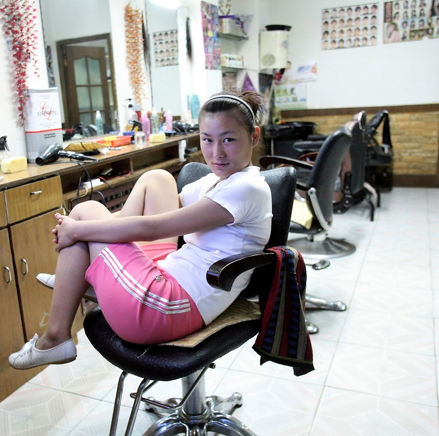A hair stylist and massage therapist waits for customers in a salon in Wuzhong in Ningxia China. Salons are often associated with prostitution in China.