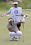 SUZHOU, CHINA - APRIL 17:   Thongchai Jaidee of Thailand lines up a putt with his caddie on the 2nd green during the Round Three of the Volvo China Open on April 17, 2010 in Suzhou, China. Photo by Victor Fraile / The Power of Sport Images