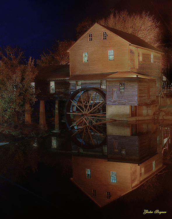 Night shot of the Old Mill in Pigeon Forge, Tennessee, reflected in the still water above the spillway. Ortonized in Photoshop. Smoky Mountain photos by Gordon and Jan Brugman.