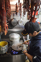 Nima Sherpa prepares dhendo for customers under a rack of sukuti (dried beef) at Dhaulagiri Kitchen, a tiny Nepalese restaurant in Jackson Heights. <br /> <br /> Danny Ghitis for The New York Times