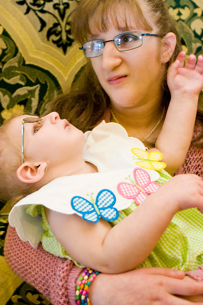 Amy Hughes holds another child afflicted with Cockayne Syndrome at the Share and Care Network's annual retreat held at the Doubletree Guest Suites Hotel in Boston on May 20, 2006. <br /> <br /> The Share and Care Network was created in 1981 by Pat Cahill when her son Scott was diagnosed with Cockayne Syndrome.  A rare form of dwarfism, Cockayne Syndrome is a genetically determined condition whose symptoms include microcephaly, mental retardation, progressive blindness, progressive hearing loss, premature aging, and a shortened lifespan averaging 18 years.  Those afflicted have distinctive facial features, including sunken eyes, pinched faces, and protruding jaws as well as distinctive gregarious, affectionate personalities.<br /> <br /> Because of the rarity of the condition (1/1,000 live births) and its late onset (characteristics usually begin to appear only after one year), many families and physicians are often baffled by children whose health begins to deteriorate after normal development.  It was partly with this in mind that the Share and Care Network was formed, to promote awareness of this disease as well as to provide a support network for those families affected.  In 1998 it began organizing an annual retreat, which has grown from three families in its inaugural year to more than 30 today.  Although the retreat takes place in the United States, families from as far as Japan arrive for this one weekend out of the year to share information and to support one another.