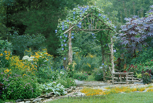 Handbuilt garden arbor with morning glory vines leading into the shaded part of the garden beyond