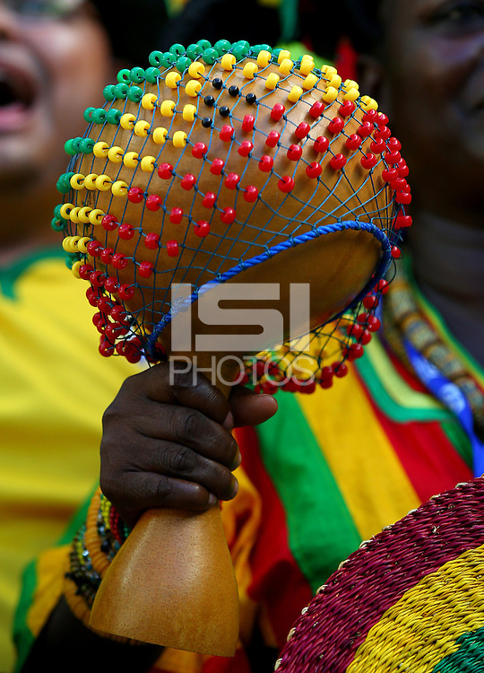 A Ghana fan holds a maraca shaped like the World Cup covered in beads of her nations colours