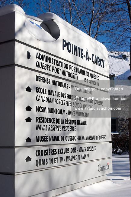 The Pointe-A-Carcy Naval Complex sign in Quebec City. Sign includes direction to the Quebec Port Authority, the Canadian Force Fleet School Quebec, the HMCS Montcalm, the Naval Reserve Residence, the Naval Museum of Quebec, River cruises and Warves 14 and 19.