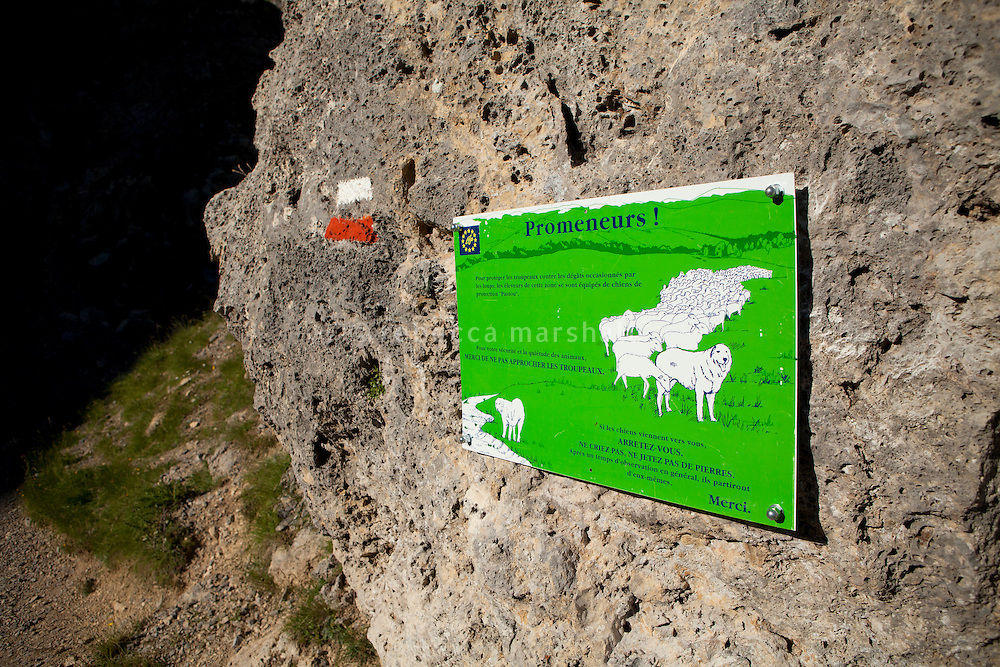 "A sign beside the footpath leading to the Plateau de Longon warns hikers about the patou dogs that protect flocks of sheep grazing on the mountain, Mercantour National Park, French Alps, France, 01 August 2013. The sign reads ""If the dogs come towards you, stop. Don't shout, don't throw stones. After observing you for a while, they [the dogs] will generally leave of their own accord"""