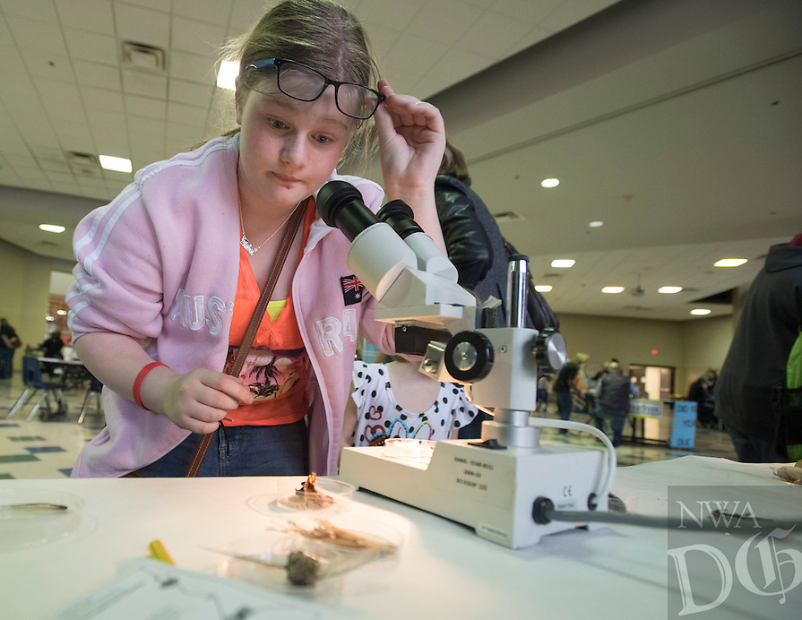 NWA Democrat-Gazette/J.T. WAMPLER Libby Christian, 11, puts a piece of coral on a microscope Thursday Mar. 10, 2016 at Old High Middle School's  Arts and Academic Night. School groups and community partners set up educational displays for visitors to enjoy. Christian is a sixth grader at the school.