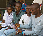 A young man in Lagos, Nigeria, talks ernestly to his out-of-school peers about HIV prevention, using educational materials designed for low literacy audiences by the Society for Family Health (SFH).   SFH is Nigeria's largest indigenous non-profit and affiliate of the international social marketing organization, Population Services International (PSI).