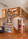 A unique wall of bookshelves surround the staircase and reading nook in a contemporary cottage. This image is available through an alternate architectural stock image agency, Collinstock located here: http://www.collinstock.com
