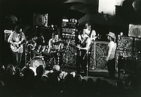 "The Grateful Dead in Concert at Yale Bowl New Haven CT on July 31, 1971. Ronald C. ""Pigpen"" McKernan on Stage facing the rest of the Band. Also Seen in this Photograph: Jerry Garcia, Bob Weir, Phil Lesh and Bill Kreutzmann. Identity of Photographer Unknown. Negative in the Anderson Photography Archives since approx 1973"