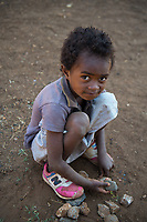 Africa, Madagascar, Ambositra city. Girl playing with rocks as toys.