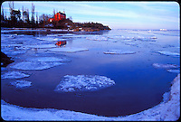 THE MARQUETTE LIGHTHOUSE AND ITS RELECTION IN OPEN WATER BETWEEN ICE FLOES ON LAKE SUPERIOR IN WINTER IN MARQUETTE MICHIGAN.