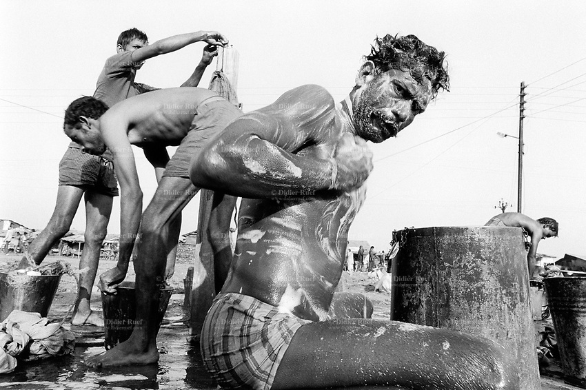 India. Province of Gujarat. Alang. Workers, all men, enjoy a day rest on the sunday. They wash themselves with soap and clean their clothes by hand. Alang, located in the Gulf of Khambhat, is a ships breaking place and is considered as the biggest scrapyard in the world. © 1992 Didier Ruef