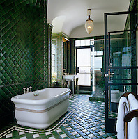 A large Victorian-style free-standing bath in a bathroom with walls covered from floor to ceiling in green tiles and with a green and white tiled floor