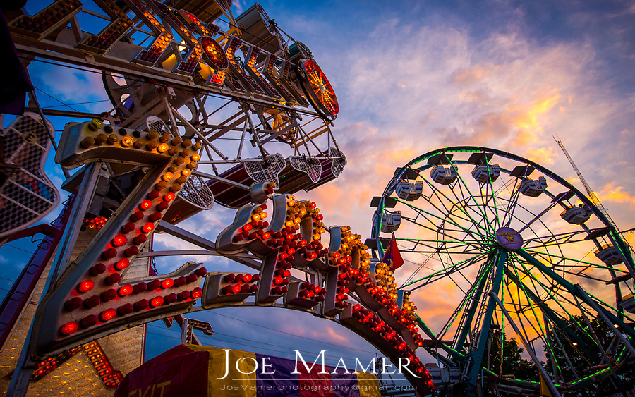 Amusement rides at a county fair at sunset.