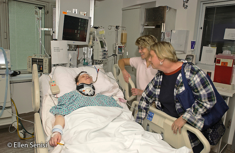 MR / Albany, New York.Albany Medical Center / Surgical Intensive Care Unit.Woman (38, Down Syndrome) recovering in ICU after spinal operation is visited by her sisters (50, 43). She is wearing a collar to keep vertebrae (C1, C2, C3) in place till healed. Spinal condition she was operated on for (os ondontoideum) is relatively rare but occurs with higher frequency among Down Syndrome people than in the general population. MR: Bab3 Kol4 She7. Note: original image name has been changed - it was previously AE-FM_0231. ©Ellen B. Senisi