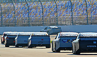 A line of cars waits on pit road as another car races past during NASCAR Sprint Cup winter testing at Daytona International Speedway, Daytona Beach, FL January 20, 2011.  (Photo by Brian Cleary/www.bcpix.com)