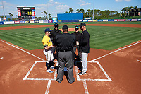 Michigan Wolverines head coach Erik Bakich (23) and  Army head coach Jim Foster (right) during the lineup exchange with umpires Kyle Reese (center), Mark Spicer (right), and Bob Lothian (left) before a game on February 17, 2018 at Tradition Field in St. Lucie, Florida.  Army defeated Michigan 4-3.  (Mike Janes/Four Seam Images)