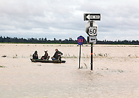 "From left, April Gensler, Josh Sherfield and Steve Hyten cross the westbound lanes of US 60 in Essex, MO on Wednesday, April 27, 2011. The group unsuccessfully tried to reach Gensler's home to collect some belongings left behind during evacuation the day before. ""The current was just too strong for our motor,"" said Gensler. ""If the current wasn't so bad, we would've made it."""