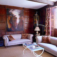 The wood-panelled living room is furnished with two re-upholstered antique sofas and an abstract canvas