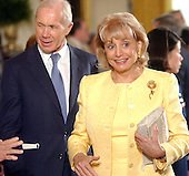 Barbara Walters and an unidentified guest depart the Presidential Medal of Freedom ceremony in the East Room of the White House in Washington, DC  on 9 July, 2002.<br /> Credit: Ron Sachs / CNP