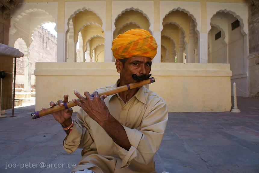 musician playing flute on courtyard of Fort Mehrangarh,  Jodhpur, Rajastan, India