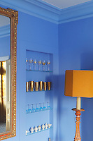 Open glass shelving in a corner of the dining room displays a collection of blue and gold glasses