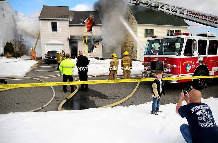 TORRINGTON, CT, 04 MAR 13- 030413AJ11- A boy has his photo taken in front of a burning home at 64 Griswold St. in Torrington Monday afternoon.  Alec Johnson/ Republican-American
