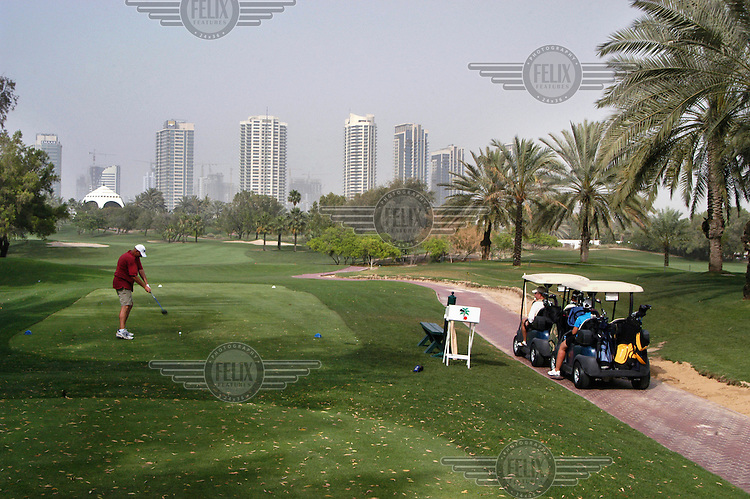 A man tees off at the Emirates Golf Club..